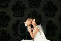 Les beaux couples dans l'amour embrassant près du mur Photo libre de droits