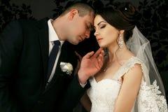 Les beaux couples dans l'amour embrassant près du mur Photographie stock