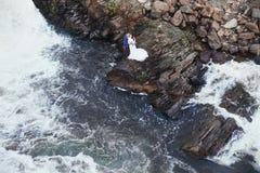 Les beaux couples dans l'amour embrassant tout en se reposant sur des roches s'approchent de la mer Images stock
