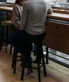 Les beaux couples dans l'amour tiennent des mains dans le restaurant Photos stock