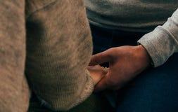Les beaux couples dans l'amour tiennent des mains dans le restaurant Images stock