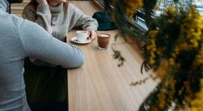 Les beaux couples dans l'amour tiennent des mains dans le restaurant il y a chocolat sur la table, les boissons café, thé de fill Photos stock