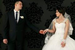 Les beaux couples dans l'amour tiennent des mains près du mur Photos stock
