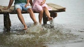 Les beaux couples de youn se reposent sur le pilier près du lac faites l'éclaboussure par des pieds Mouvement lent banque de vidéos