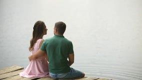 Les beaux couples de youn se reposent sur le pilier près du lac L'atmosphère romantique clips vidéos