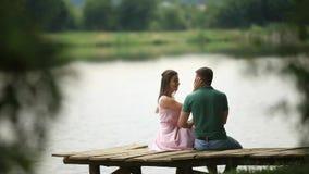 Les beaux couples de youn se reposent sur le pilier près du lac L'atmosphère romantique Biew arrière banque de vidéos