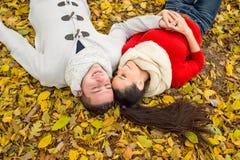 Les beaux couples en automne garent le mensonge au sol Photographie stock libre de droits