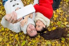 Les beaux couples en automne garent le mensonge au sol Photos libres de droits
