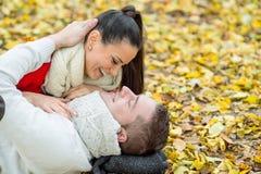 Les beaux couples en automne garent le mensonge au sol Photo libre de droits