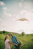 Les beaux couples sourient au cerf-volant d'air avec le dragon de ciel Photo libre de droits
