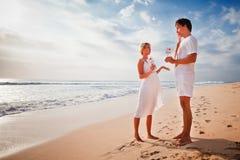 Les beaux couples sur la plage tiennent le cadre avec des signes de l'amour et du coeur Photographie stock