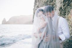 Les beaux couples sur le bord de mer se sont fermés dans un voile, riant, souriant, heureux, épousant, histoire d'amour Photo stock