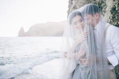Les beaux couples sur le bord de mer se sont fermés dans un voile, riant, sourire, heureux, jour du mariage, amour Images libres de droits