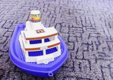 Les beaux enfants jouent le bateau en plastique bleu et blanc photos stock