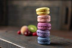 Les beaux et savoureux biscuits français de macaron se tiennent sur un support en bois à côté du fruit Dîner romantique derrière  photo libre de droits