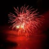 Les beaux feux d'artifice colorés sur l'eau apprêtent avec un fond noir propre Festival d'amusement et concours international de  Image stock