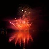 Les beaux feux d'artifice colorés sur l'eau apprêtent avec un fond noir propre Festival d'amusement et concours international de  Photos stock