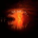 Les beaux feux d'artifice colorés sur l'eau apprêtent avec un fond noir propre Festival d'amusement et concours international de  Photos libres de droits