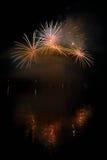 Les beaux feux d'artifice colorés sur l'eau apprêtent avec un fond noir propre Festival d'amusement et concours international de  Photographie stock libre de droits