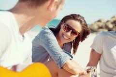 Les beaux jeunes avec la guitare sur la plage Images stock