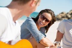 Les beaux jeunes avec la guitare sur la plage Image libre de droits