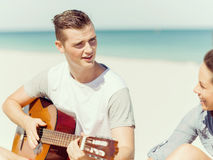 Les beaux jeunes avec la guitare sur la plage Image stock