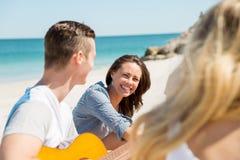 Les beaux jeunes avec la guitare sur la plage Photo stock