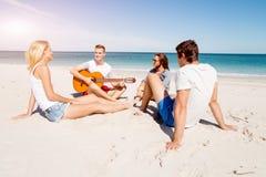 Les beaux jeunes avec la guitare sur la plage Images libres de droits