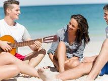 Les beaux jeunes avec la guitare sur la plage Photos libres de droits
