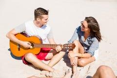 Les beaux jeunes avec la guitare sur la plage Photos stock