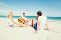 Les beaux jeunes avec la guitare sur la plage Photographie stock