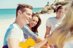 Les beaux jeunes avec la guitare sur la plage Photo libre de droits