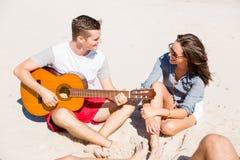 Les beaux jeunes avec la guitare sur la plage Photographie stock libre de droits