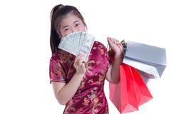 Les beaux jeunes Chinois asiatiques d'usage de femme habillent le cheongsam ou le qipao traditionnel avec porter un billet de ban Image stock