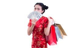 Les beaux jeunes Chinois asiatiques d'usage de femme habillent le cheongsam ou le qipao traditionnel avec porter un billet de ban Photos stock