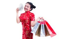 Les beaux jeunes Chinois asiatiques d'usage de femme habillent le cheongsam ou le qipao traditionnel avec porter un billet de ban Photographie stock