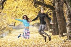 Les beaux jeunes couples célèbrent et sautant après la formation réussie en parc Photographie stock libre de droits