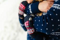Les beaux jeunes couples dans l'amour étreignant en hiver chauffent des chandails et des jeans étreignant en parc en hiver Nature Photos stock