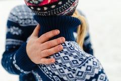 Les beaux jeunes couples dans l'amour étreignant en hiver chauffent des chandails et des jeans étreignant en parc en hiver Nature Images stock