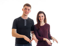 Les beaux jeunes couples de sourire se tenant près du regard redressent et montrent des gestes de mains Photographie stock libre de droits