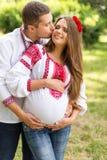 Les beaux jeunes couples enceintes se sont habillés dans le style ukrainien national embrassant en parc d'automne Concept de mate Photos libres de droits