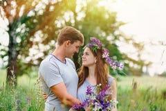 Les beaux jeunes couples font du jardinage au printemps avec un bouquet des wildflowers Photographie stock