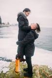 Les beaux jeunes couples ont la lune de miel romantique à la mer L'homme tient sur des mains son amie et sourire merveilleux Images libres de droits