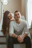 Les beaux jeunes couples romantiques équipent la femme dans étreindre d'amour, embrassant, à l'intérieur Photos stock