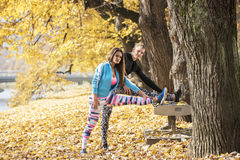 Les beaux jeunes couples s'étendant ensemble et refroidissent après la formation en parc Photographie stock libre de droits
