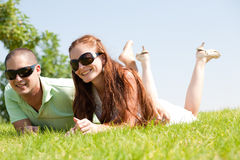 Les beaux jeunes couples se couchent sur l'herbe Photos libres de droits
