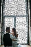 Les beaux jeunes nouveaux mariés posent sur le fond de fenêtre de vintage d'ornement Discret dessin-modèle mariage Photos libres de droits