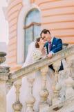 Les beaux jeunes se sont juste mariés sur des escaliers en parc Palais antique romantique au fond Photographie stock libre de droits