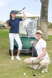 Les beaux joueurs de golf s'approchent de son véhicule de golf image stock