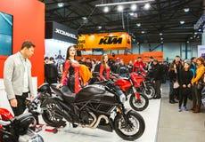 Les beaux modèles femelles font de la publicité de nouveaux vélos Ducati en The Field photographie stock